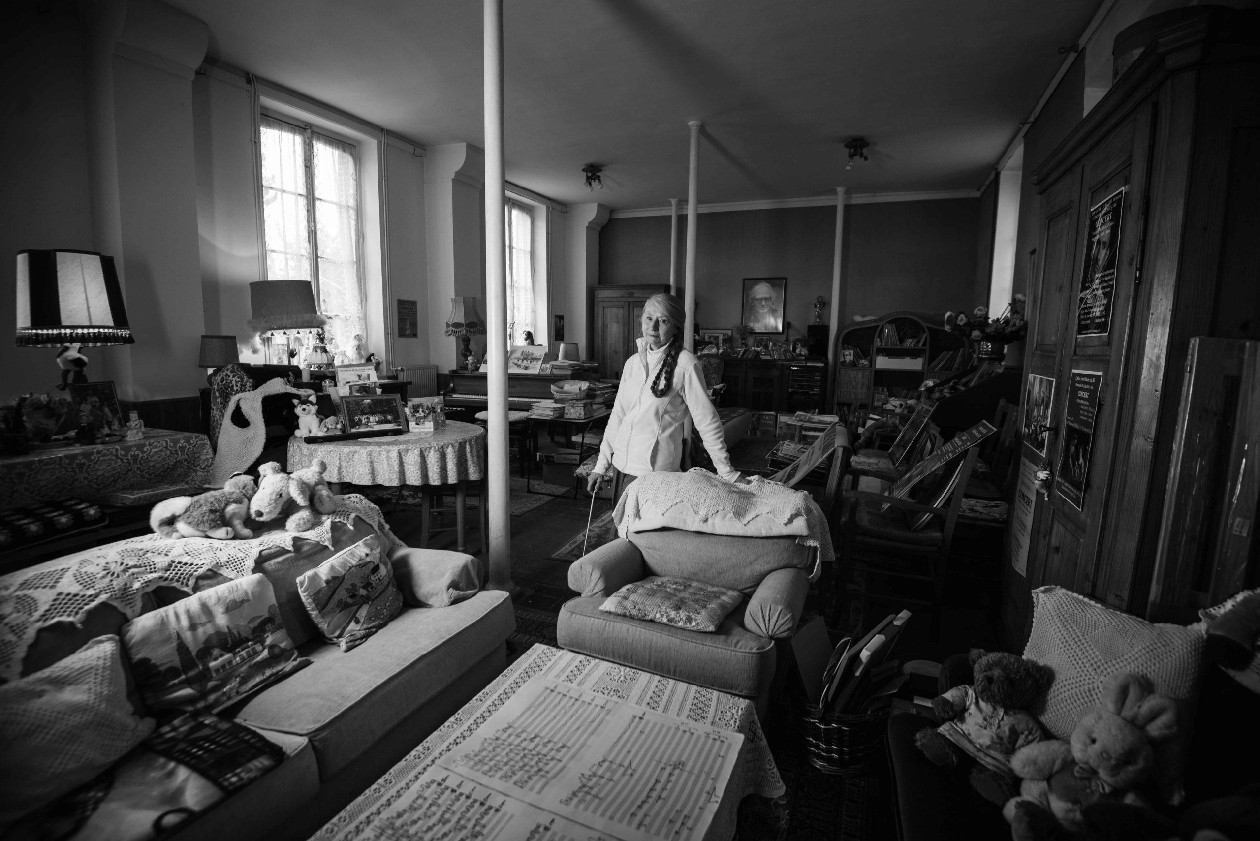 Michèle Foison se tient debout au milieu de son salon