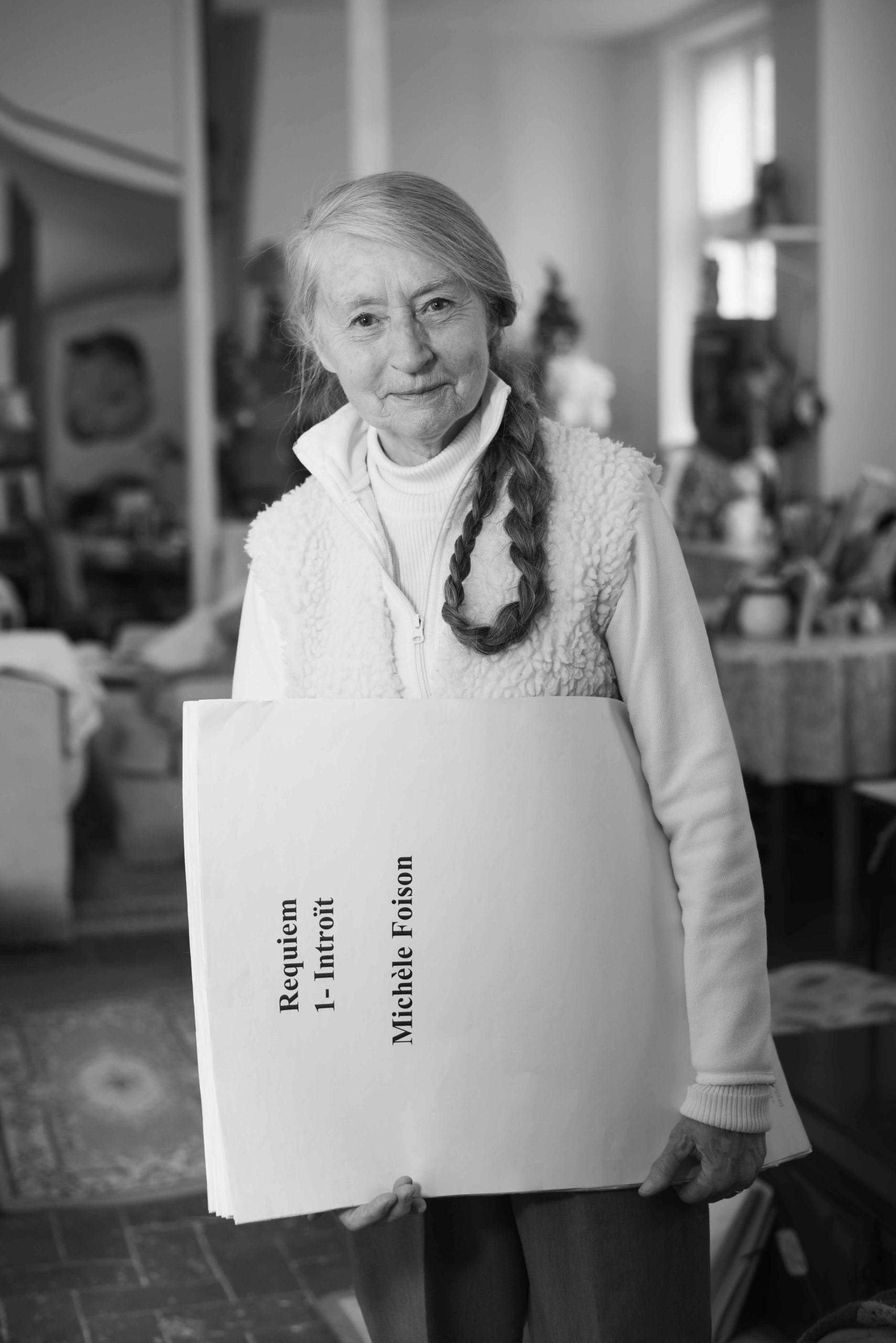 Michèle Foison se tient debout au milieu de son salon et tient la gigantesque partition de son requiem dans les bras